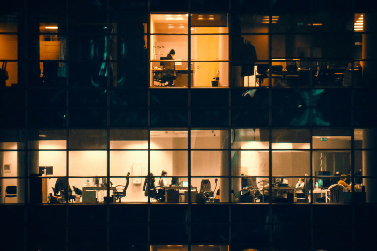 Group of people in glass building at night
