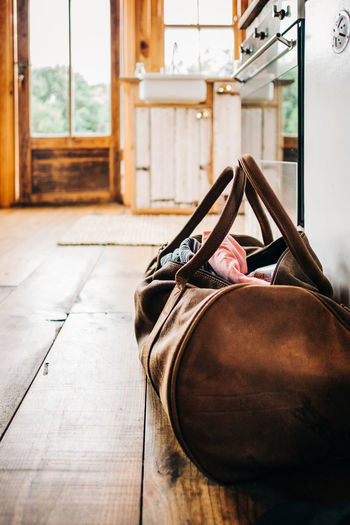 Holiday Travel Absence Bag Clothes Day Flooring Focus On Foreground Indoors  Leather Lifestyles Low Section No People Real People Shoe Still Life Window Wood - Material
