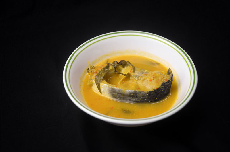 Ikan patin tempoyak Local Dish Traditionalfood Indoors  Healthy Eating Refreshment Studio Shot Black Background Close-up Ready-to-eat High Angle View DeliciousFood And Drink Patin Fish Malaysian Seafood ASIA Tumeric Spicy