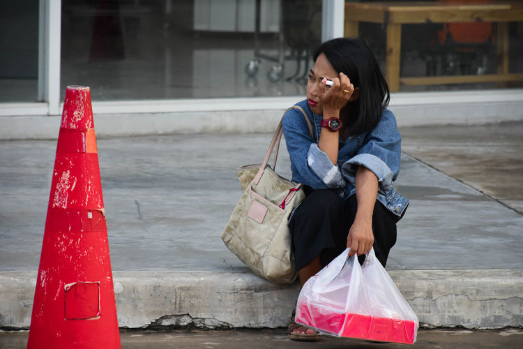 Thoughtful woman holding plastic bag while sitting by red traffic cone on road