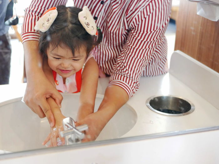 Mirror reflection of a little girl, with help from her mother, learning to wash her hands before a meal - teaching kids to wash their hands Childhood Child Lifestyles Cute Baby Girl Kid Toddler  Asian  Daughter Washing Cleaning Water Hands Hand Help Teach Mother Mom Holding Happy Enjoy Fun Sink Smiling Hygiene Restaurant Sanitory Healthcare