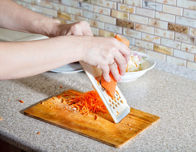 Cropped hands grating carrot in kitchen at home