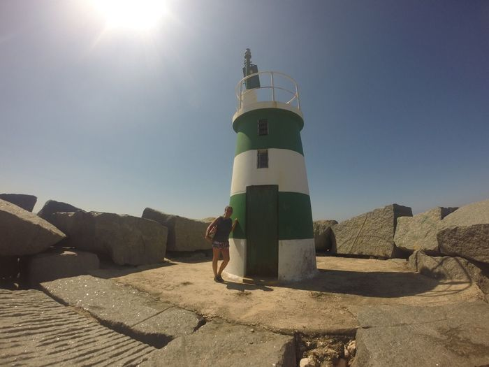 Full length of woman standing by lighthouse at alvor on sunny day