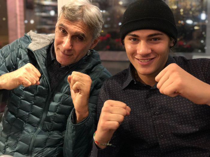 Portrait of father and son clenching fists at home