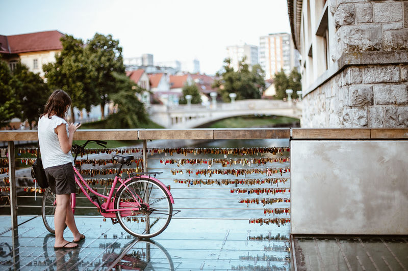 Rear view of woman with bicycle against building in city