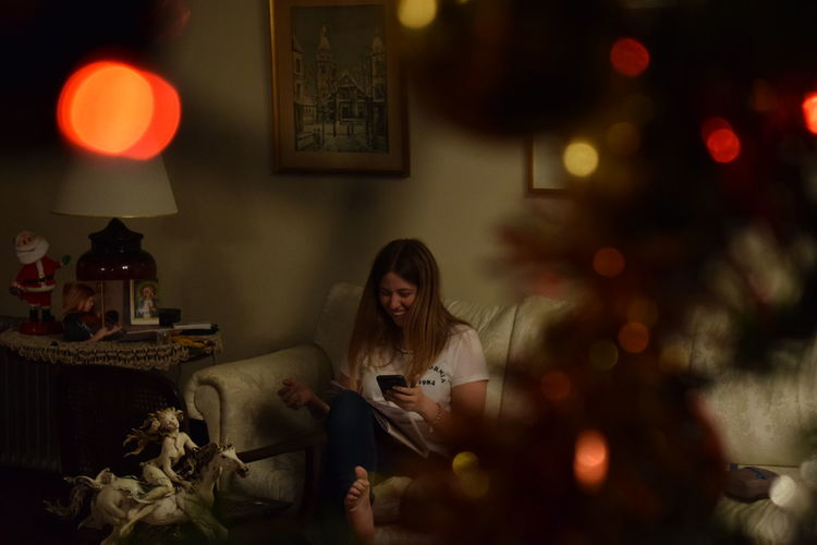 Smiling woman using mobile while sitting on sofa at home during christmas