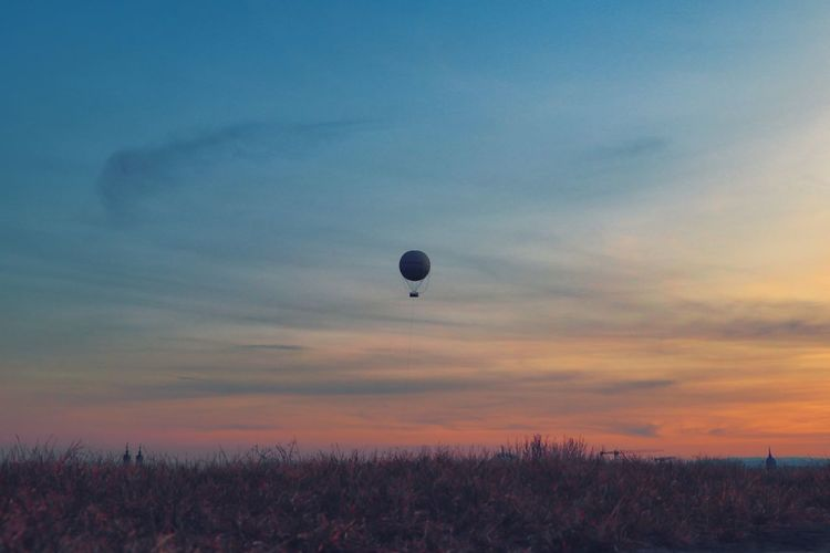 Hot air balloons on field against sky during sunset