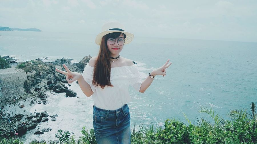 Portrait of woman gesturing peace sign while standing against sea