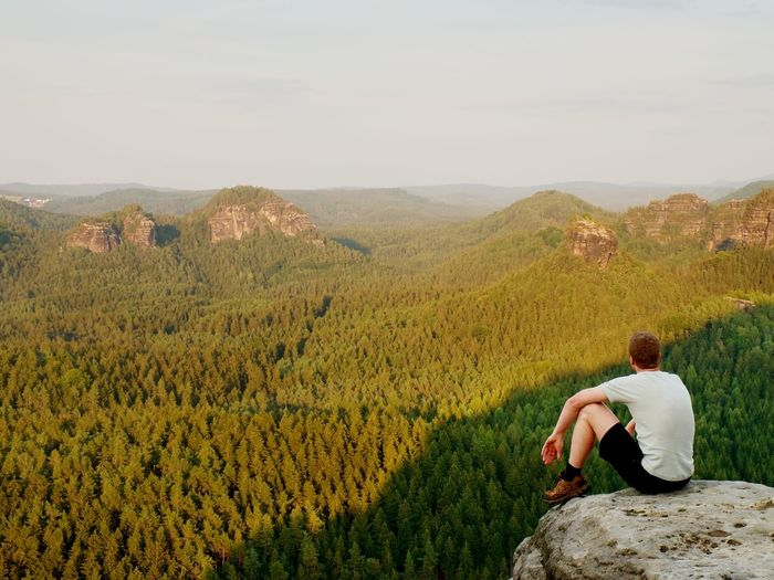 Moment of loneliness. tourist in shirt sit on the peak of rock and watching into forest valley.