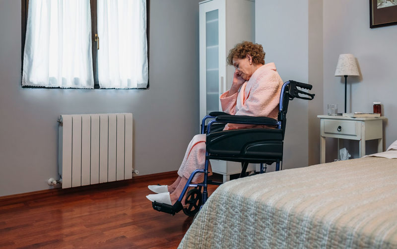 Side view of senior female patient sitting on wheelchair in hospital