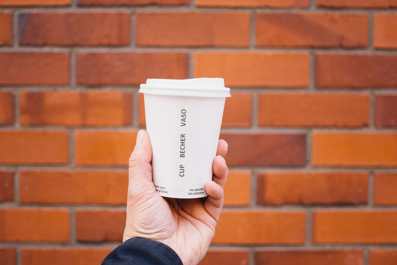 Cropped Hand Holding Coffee Cup In Front Of Brick Wall