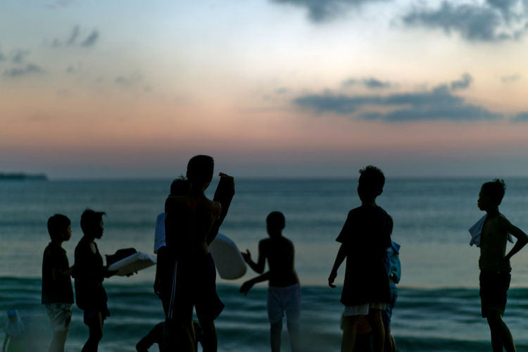 Group of kids playing at the beach during sunset Sea Sunset Sky Group Of People Water Horizon Over Water Horizon Beach Beauty In Nature Standing Silhouette Land Leisure Activity Men Real People Scenics - Nature Three Quarter Length Lifestyles Nature Outdoors Teenager Young Adult