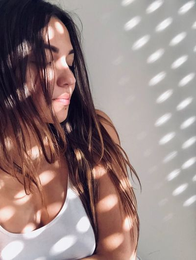 Sunlight Falling On Beautiful Young Woman With Eyes Closed Against Wall