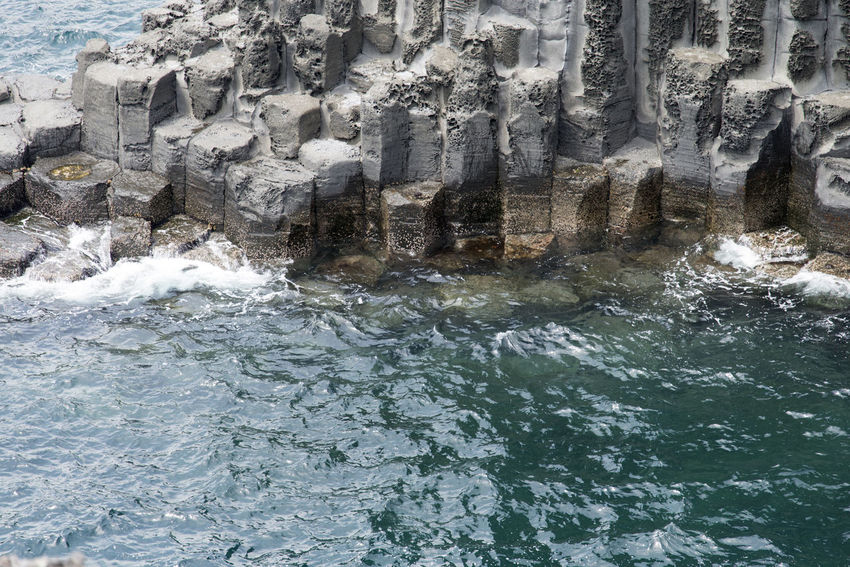 view of columnar joints (jusangjeolli) at Jungmun Tourism Complex in Jeju Island, South Korea Beauty In Nature Close-up Columnar Joints Day JEJU ISLAND  Jungmun Tourism Complex Jusangjeolli Nature No People Outdoors Rock - Object Sea Seaside Water Waterfront
