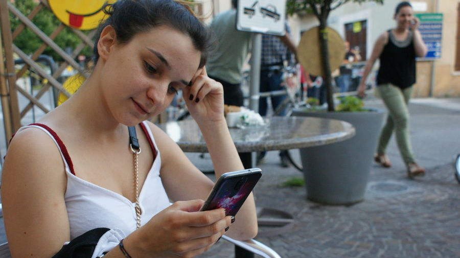 Close-up of thoughtful woman using mobile phone at sidewalk cafe