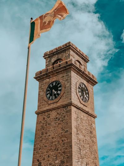 Low angle view of flag by clock tower against sky