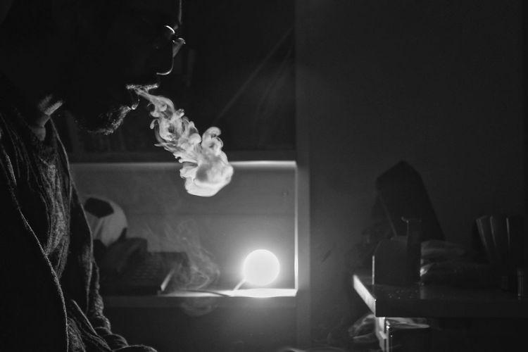 Close-up of man smoking in illuminated room