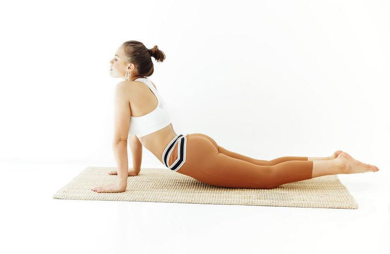 Full length of woman sitting against white background