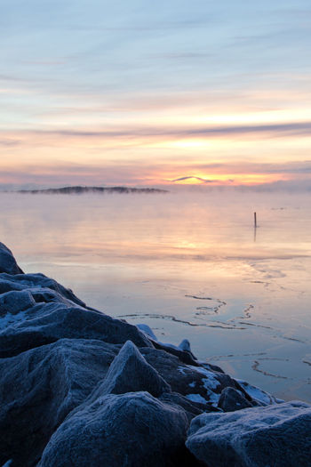 Rocks by frozen lake against sky during sunset