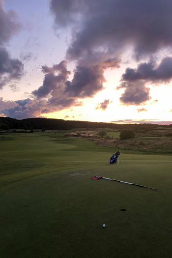 Scenic view of golf course against sky during sunset