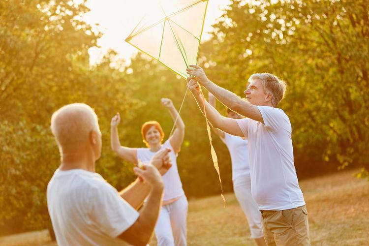 Cheerful senior friends flying kite at park