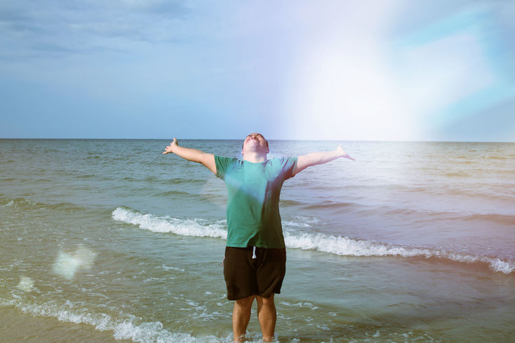 Young man very happy in the holidays. By playing the sea. Beach Beauty In Nature Clear Sky Day Front View Full Length Happiness Horizon Over Water Leisure Activity Lifestyles Mature Adult Nature One Person Outdoors Real People Sand Scenics Sea Sky Standing Tranquil Scene Tranquility Vacations Water Wave EyeEm Ready   An Eye For Travel
