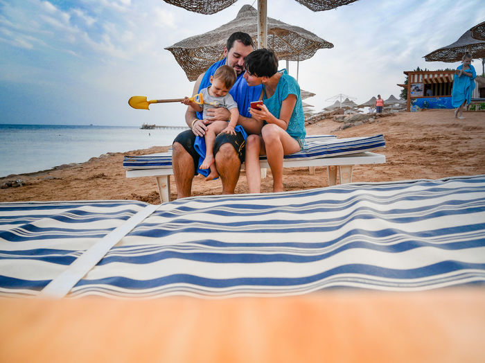 Family Sitting On Lounge Chair At Beach Against Sky