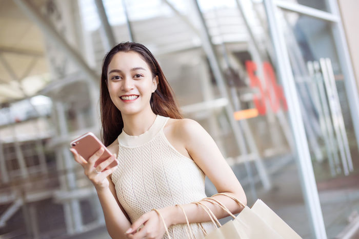 Young women relax and fun with shopping Beautiful Happiness Joyful Market Relaxing Sale Shopping Bag Cheerful Discount Happiness Holding Lifestyles Looking At Camera Mall Order Paper Portrait Relax Shop Smart Phone Store Women Young Adult Young Women