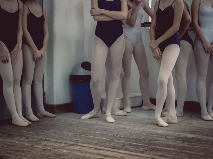 Low Section Of Ballet Dancers Standing On Wooden Floor