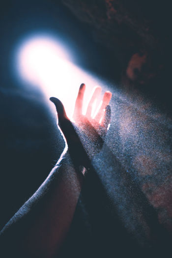 Cropped of hand amidst light penetrating through hole