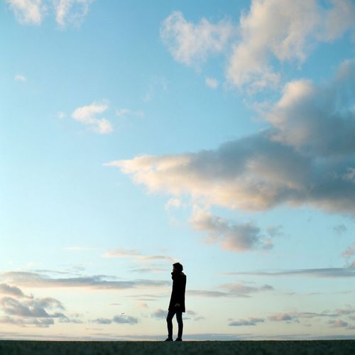 Rear view of silhouette woman standing against sky