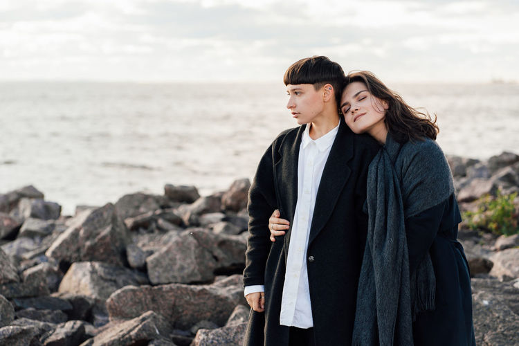 Young couple standing on rock by sea against sky