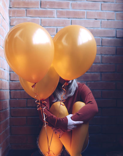 Woman With Balloons Sitting Against Wall