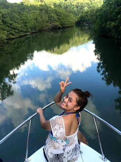 Portrait of woman showing peace sign while sitting on yacht bow in lake