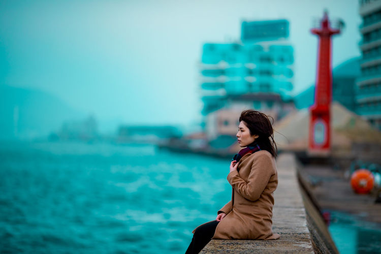 Side view of woman against sea in city