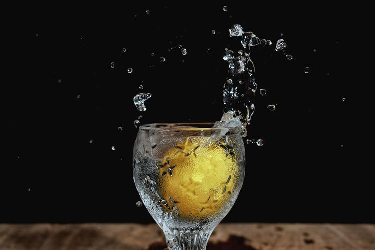 Close-up of water splashing on glass against black background