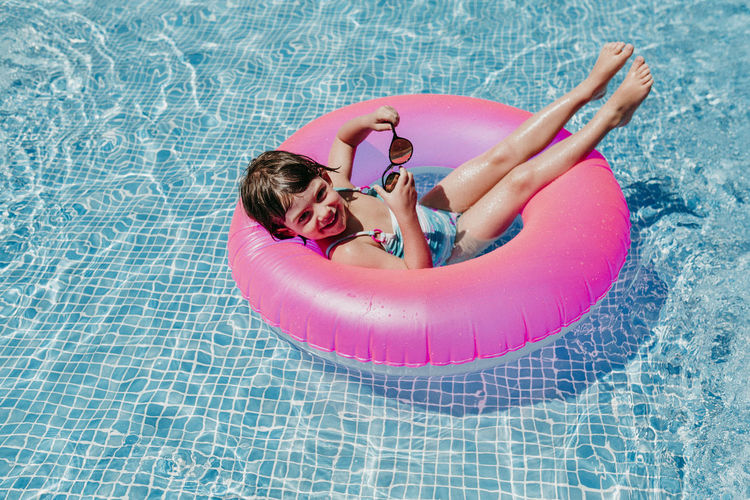 Portrait of smiling girl with inflatable ring in swimming pool