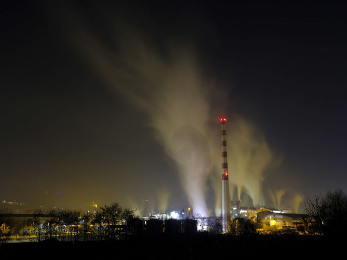 Smoke emitting from factory against sky at night