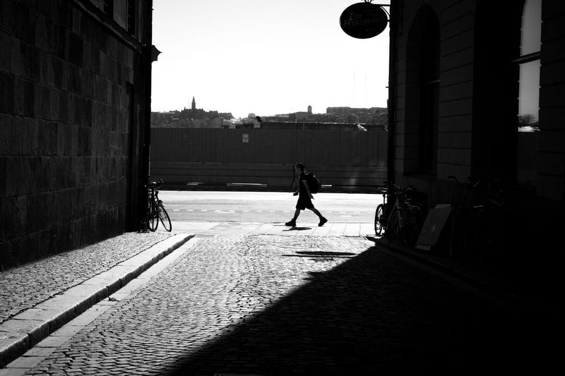 Silhouette man walking on street amidst buildings in city