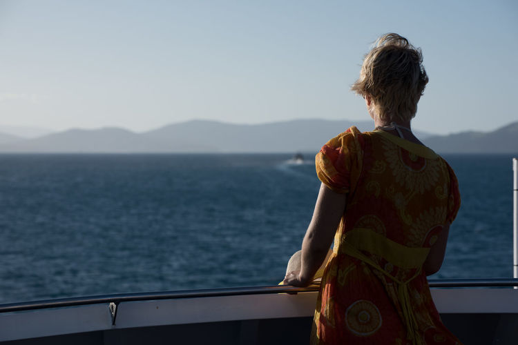 Rear view of woman standing in boat at sea against sky