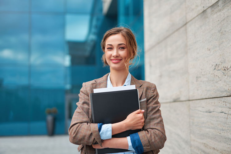Portrait of smiling businesswoman standing outdoors