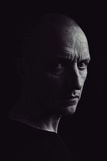 Close-up portrait of serious man against black background