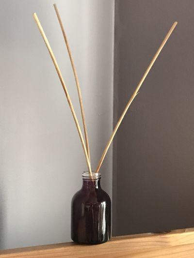 Close-up of sticks in bottle on table