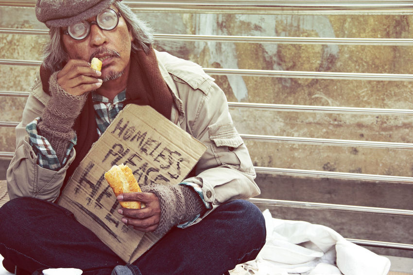 Homeless man on street and eating old bread. Adult Casual Clothing Communication Eating Food Food And Drink Front View Holding Indoors  Lifestyles Males  Mature Adult Mature Men Men One Person Real People Relaxation Sitting Snack Social Issues Three Quarter Length