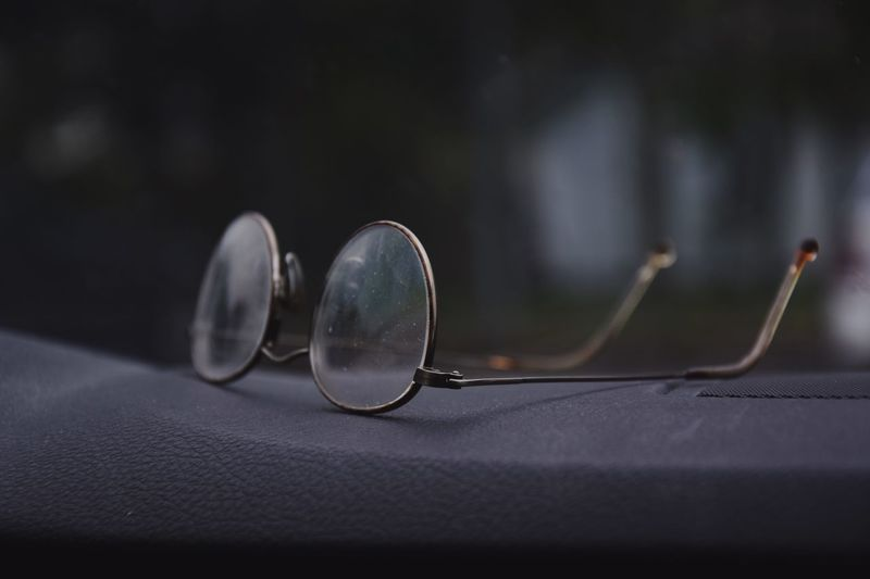 Close-up of eyeglasses on dashboard in car