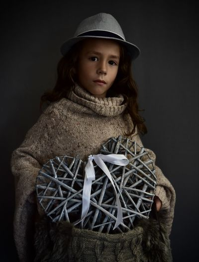 Portrait of cute girl wearing hat against black background