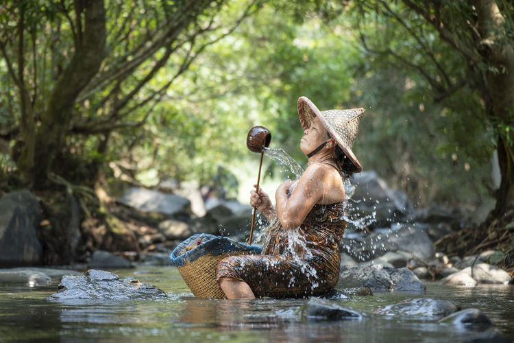 Senior woman taking bath while sitting on rock in river