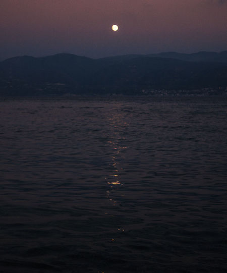 Sky Tranquility Water Tranquil Scene Beauty In Nature Scenics - Nature Moon Waterfront Nature No People Mountain Sunset Environment Remote Idyllic Sea Outdoors Dusk Non-urban Scene