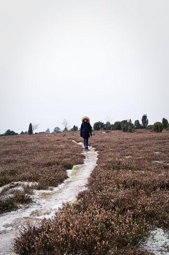 Woman wearing hood standing on footpath against clear sky