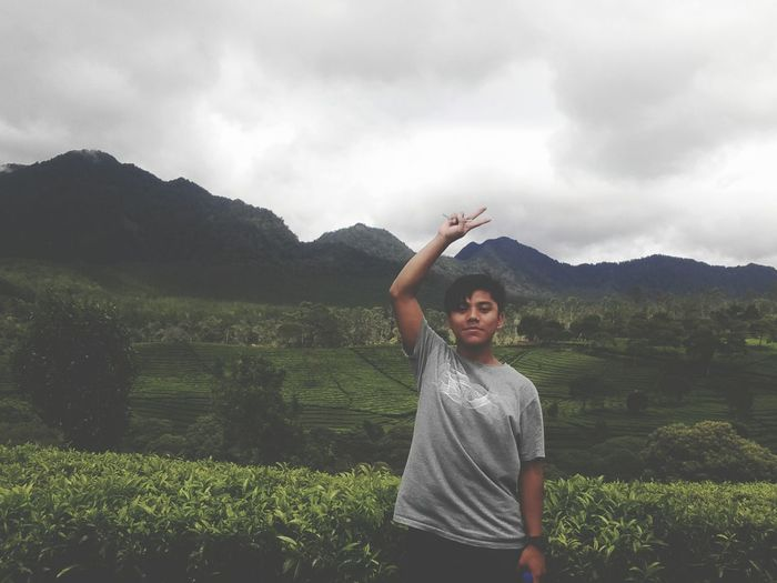 Portrait of teenage boy showing peace sign while standing against mountains